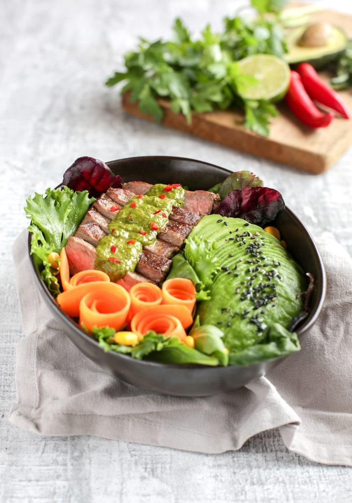 irish steak salad bowl with avocado, carrots, green leaves and chimichurri sauce