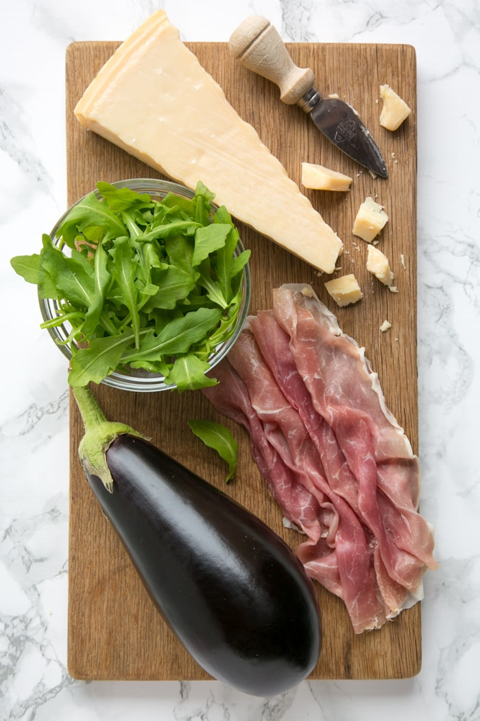 Eggplant, prosciutto, grana padano cheese, cheese knife and rocket leaves in glass bowl all placed over a wood board