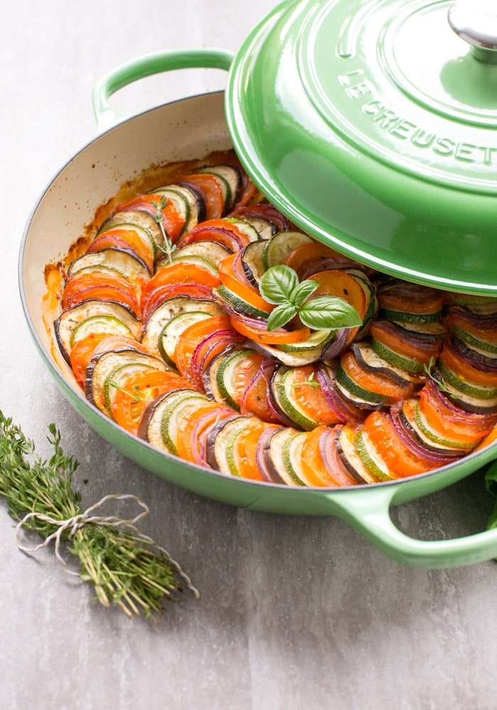 Easy Ratatouille in a large green cast iron shallow pan with lid on the side, bunch of thyme sprigs on the left side and a green napkin on the top right side.