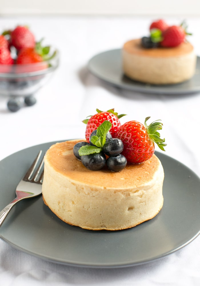 Japanese pancakes topped with strawberries and blueberries and fork next to it, on grey plate and white tablecloth