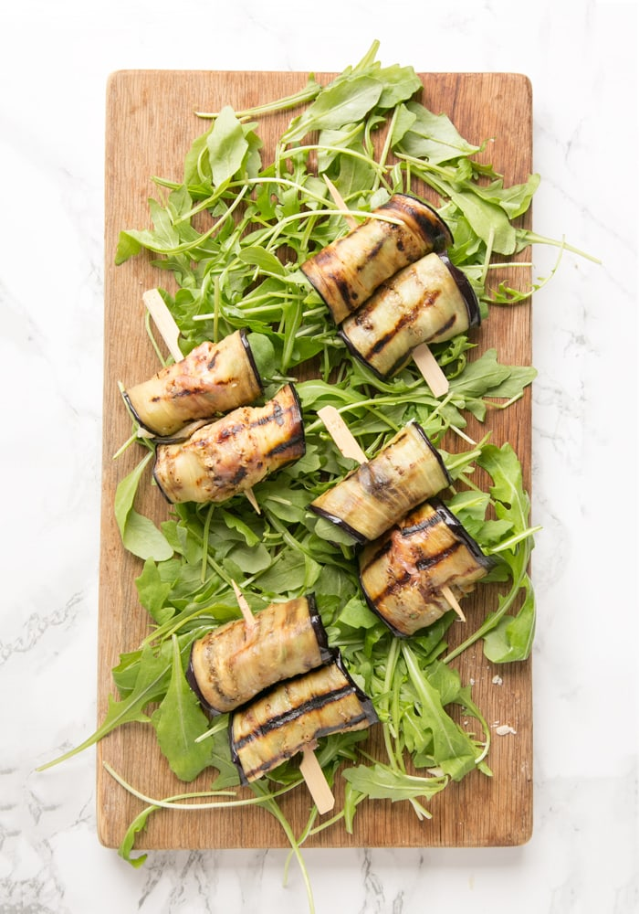 eggplant roll-ups over a bed of rocket leaves on a wood board