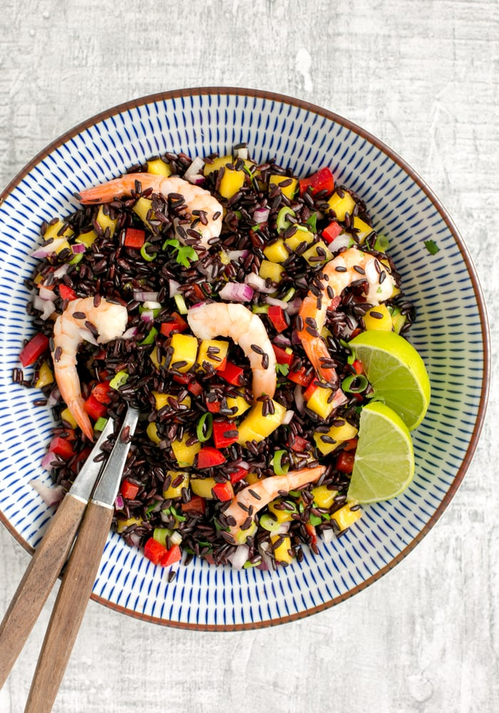 venere black rice salad with shrimps and mango salsa in a bowl