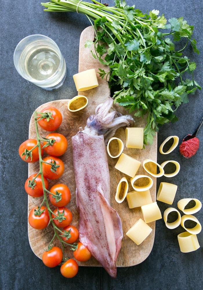 fresh calamari, cherry tomatoes, calamarata pasta, parsley, tomato pasta and glass of wine