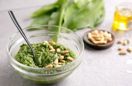 wild garlic pesto topped with pine nuts in a small glass jar