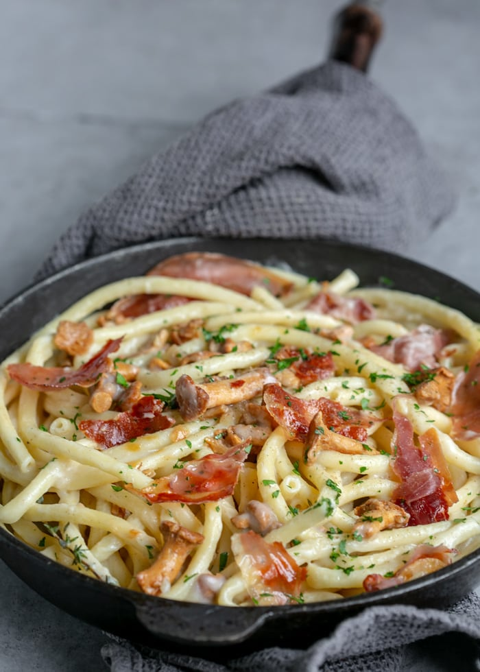 Creamy Pasta with Chanterelle Mushrooms and Crispy Prosciutto in cast iron skillet with a grey towel covering the handle