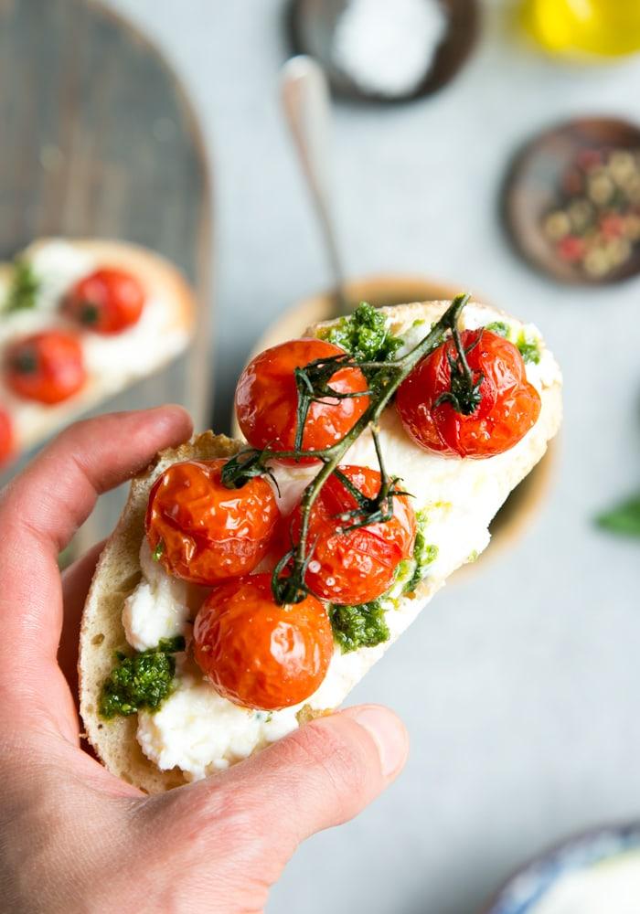 hand holding a bruschetta with confit tomato bruschetta with ricotta and basil pesto