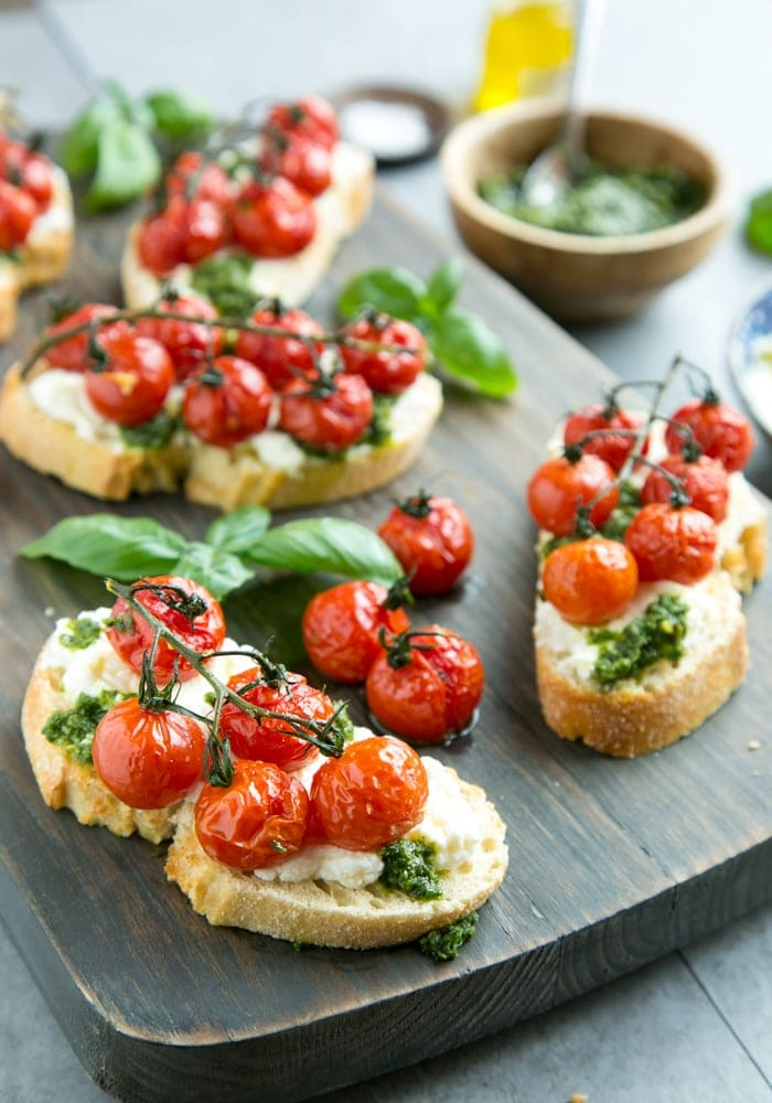confit tomato bruschetta with ricotta and basil pesto over a wood board