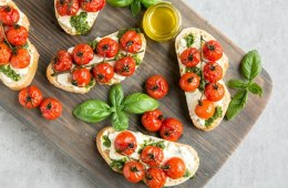 Cherry tomato confit bruschetta with ricotta and basil pesto over wood board