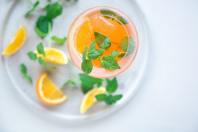 italian orange spritz in large wine glasse decorated with orange slice and fresh mint leaves