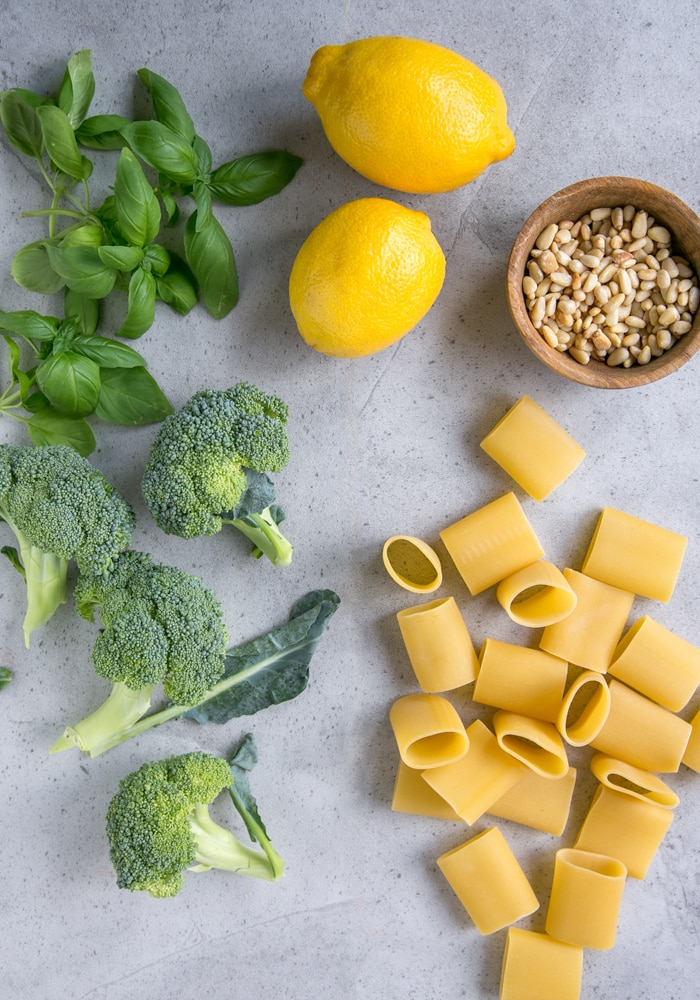 broccoli, basil, lemons, paccheri pasta and toasted pine nuts on grey board