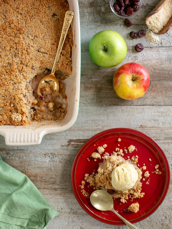 On the right down side, vegan apple crumble on a red plate topped with vanilla ice cream and a spoon next to the plate. On the top right side 2 apples, one green and one red, cranberries in a small glass pot and some almond flour scattered over the counter. On the top left side, apple crumble in a baking dish with a gold spoon.
