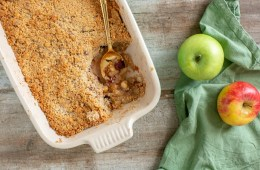 vegan apple crumble in a baking dish with a golden spoon, one red apple and one green apple on the right side over a green napkin.