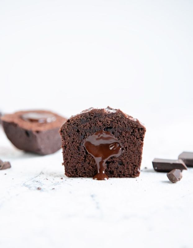 vegan chocolate muffin cut into half with chocolate pouring from the center, chocolate chunks and the remaining halved muffin in the background