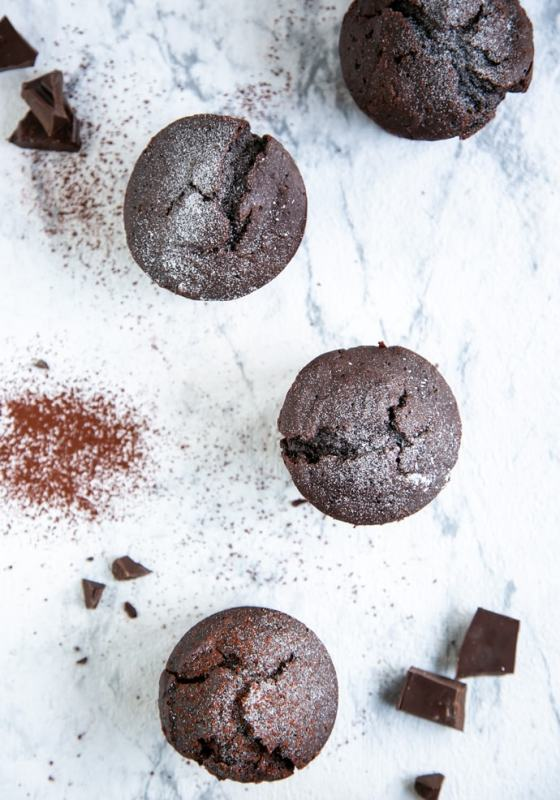 four vegan chocolate muffins over white marble background, cocoa powder and chocolate chunks sprinkled over
