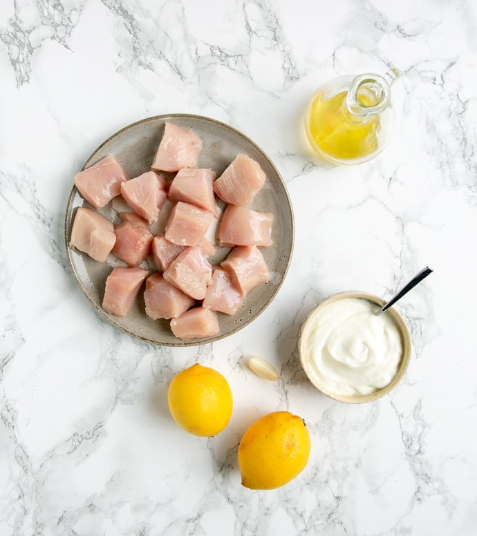 chicken cubes onto a grey plate, two lemons, one garlic clove, yogurt in a small pot with a teaspoon and olive oil in a glass bottle