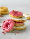 Four strawberry-Lemon gluten-free baked donuts on top of each other, one doughnut on the left side, and more doughnuts in the background