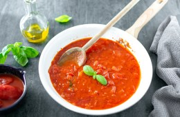 italian tomato sauce in a white pan with a wood spoon, next to a grey napkin on the right side, on the left side a small bowl with canned tomatoes, basil leaves and a small glass bottle of extra-virgin olive oil.