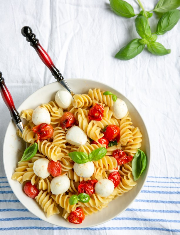 Italian caprese pasta in a large white bowl with serving spoons, basil leaves in the background