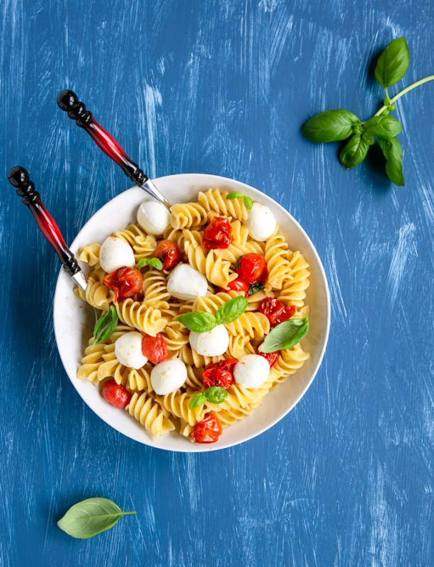 Italian caprese pasta in a large plate with serving spoons, basil leaves scattered over the blue background