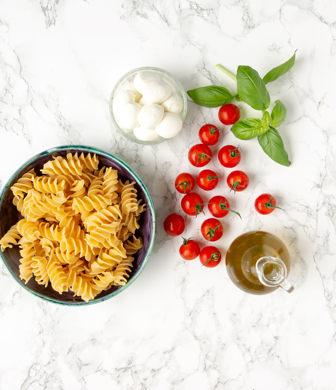 fusilli pasta in a large light blue pasta bowl, mozzarella balls in a small bowl, olive oil in glass bottle, basil leaves and cherry tomatoes scattered around the marble background