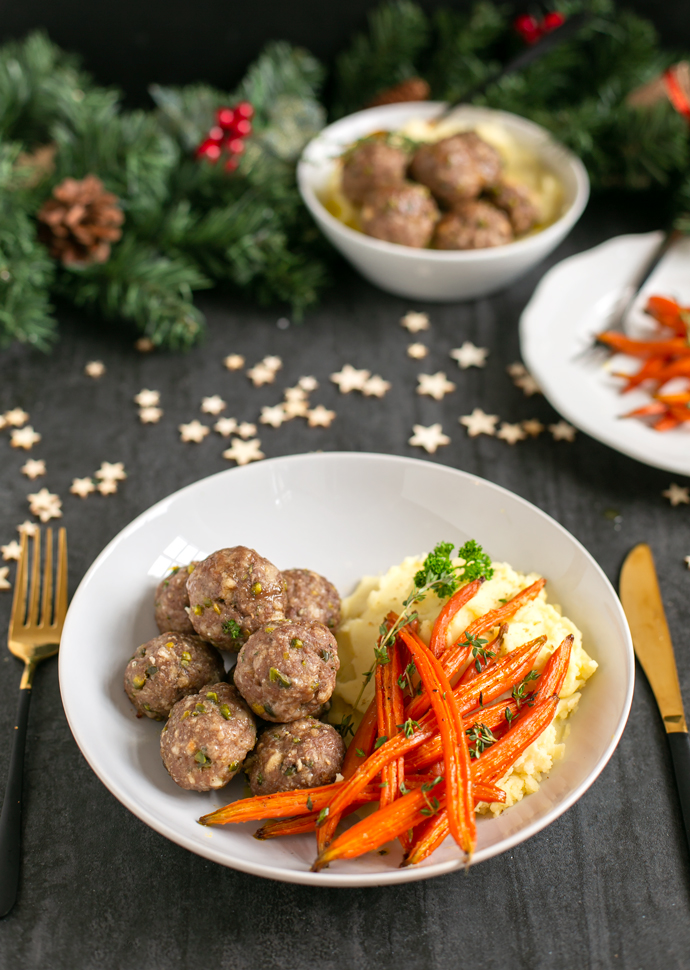 pistachio lamb meatballs served on a white dish together with glazed carrots and mashed potatoes
