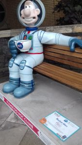 Wallace dressed as a space man sitting with a cup of tea