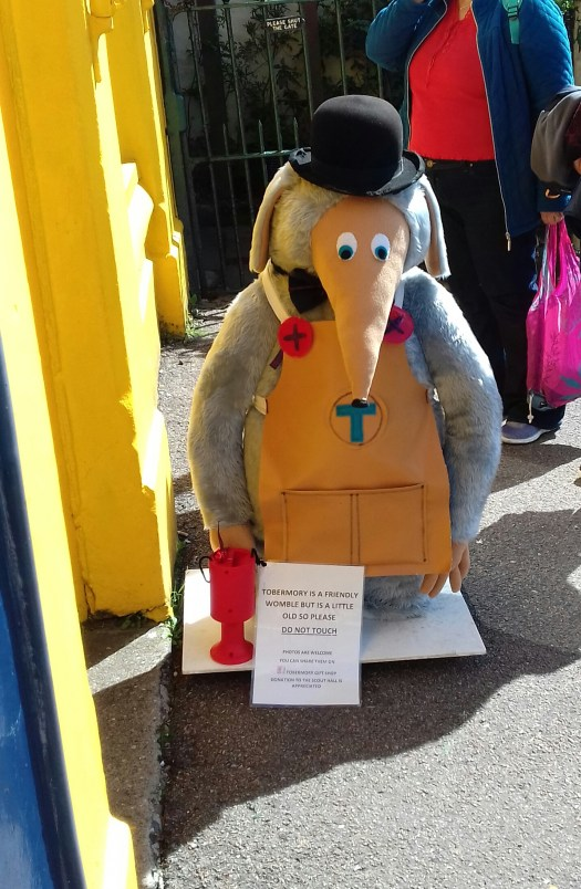 A photo of the womble Tobermory outside a shop in Tobemory