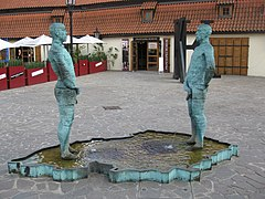 This shows two men urinating into a pool shaped like a map of Czechia