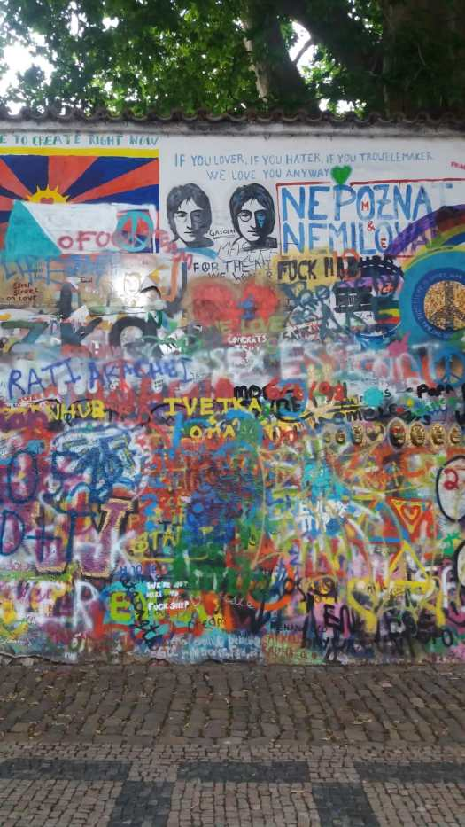 This shows a section of wall covered in spray paint with very prominant paintings of John Lennon