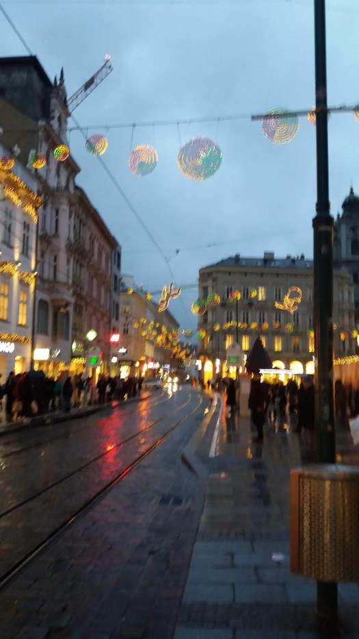 A rainy street with christmas lights
