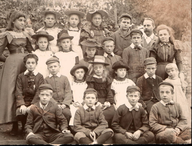 A school photo with boys in suits and girls in pinafore dresses.