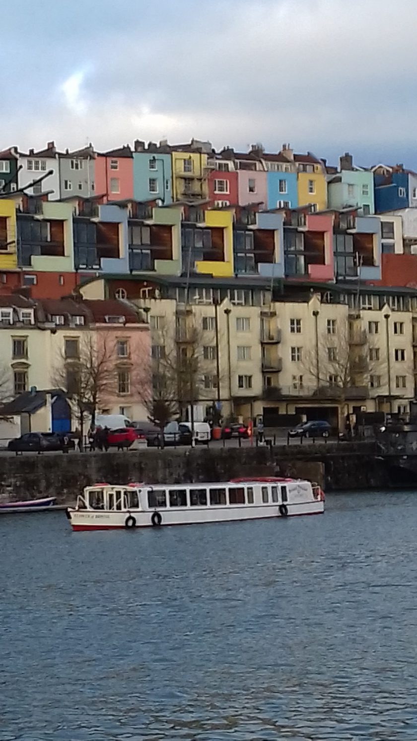 A boat passing the colourful houses on Bristol harbourside