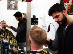 Mo trims Joe's hair.