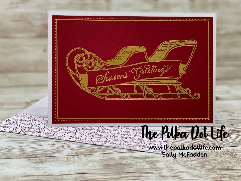 A photo of a Christmas greeting card featuring a red background and a golden sleigh.