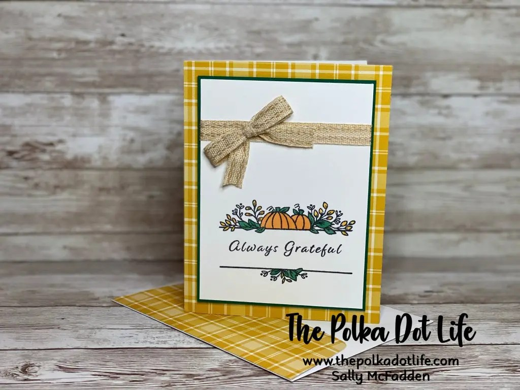 A fall greeting card that uses a golden colored plaid paper.There is an image of a pumpkin on the front.