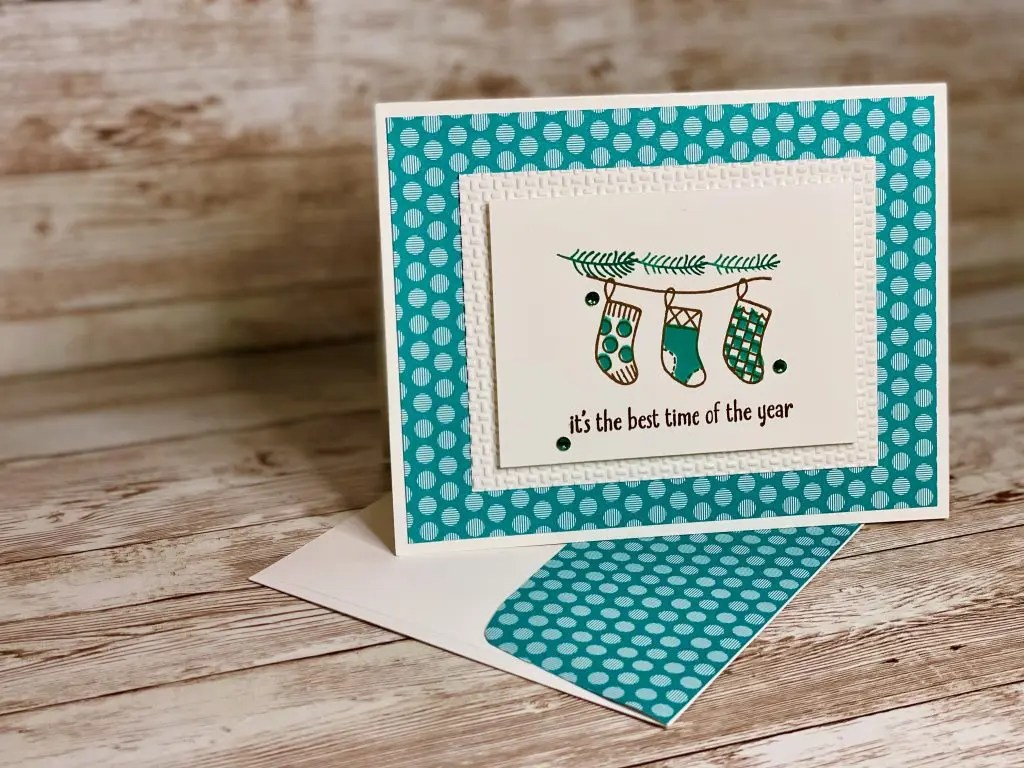 This greeting card has a super cute vibe.  It is Bermuda Bay in color and it is covered with polka dots.The focal image has three stockings hanging from some greens.