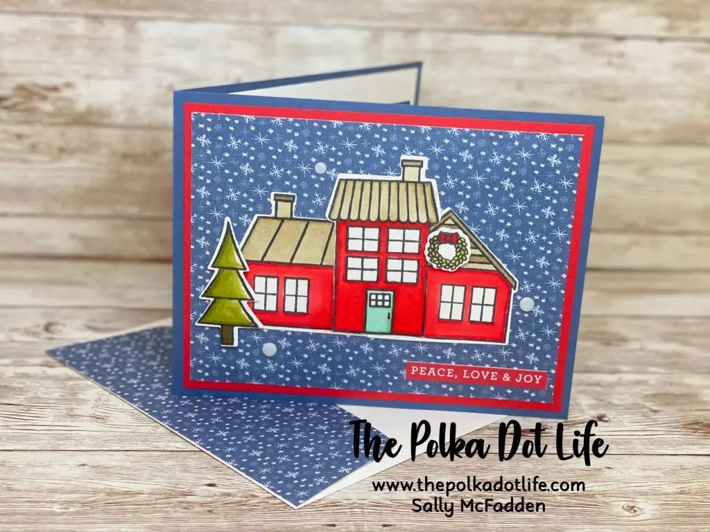This is a bright blue and red Christmas card, It has a whimsical image of a house on the front.