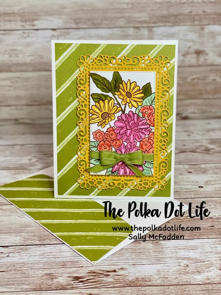 A greeting card on a Whisper White base with a striped Old Olive background.  It has a large image of a group of flowers on the front. It is a fun fold card.
