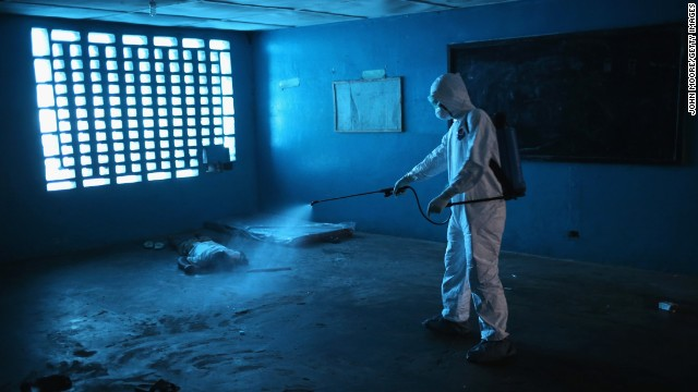 A worker disinfects a deceased Ebola patient.