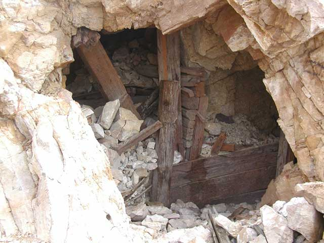 This photo illustrates another adit that is unsafe to enter.  Note the collapsed post and cave in. The structural integrity of this mine is zero.