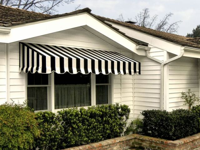 Shading windows with a short but deep awning and sheer tier curtains to reduce heating from sunlight.
