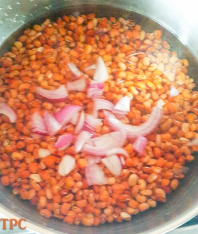 beans with sliced onions cooking in a pot for Adalu, beans and corn porridge
