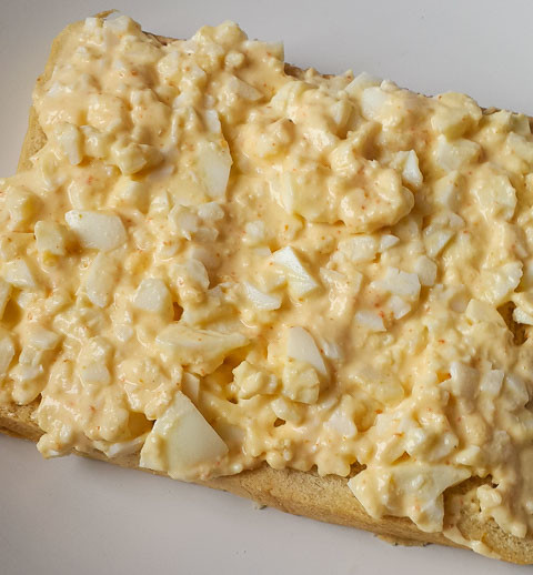 mashed egg and mayonnaise on slice of bread for boiled egg sandwich