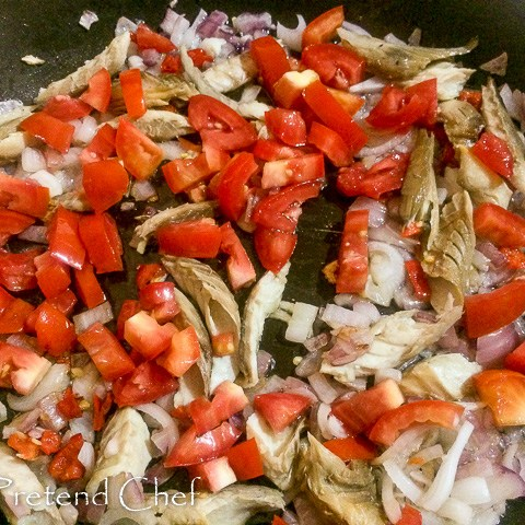 smoked fish with greens frying in a saucepan