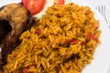 Nigerian coconut jollof rice in a plate with fish and vegetables