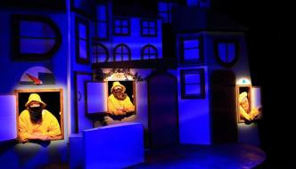 Puffin Island on stage: a blue light showing nighttime is on the stage houses as three bearded figures peer out of windows in yellow waterproof coats