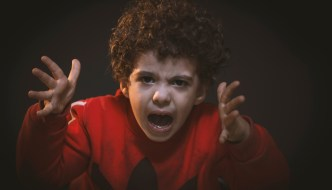 angry toddler with a red jumper reaching upwards
