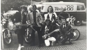 Black and white photo of the original Rocket 88 line up with a motorbike and a Rocket 88 camper van in the background