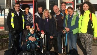 Teignmouth Railway Station is in the background as a group of people stand behind the bin bags from their clean up