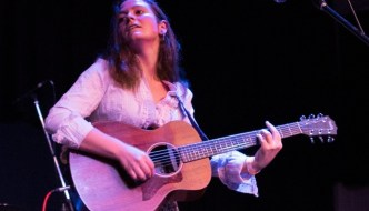 emily howard on stage with a guitar